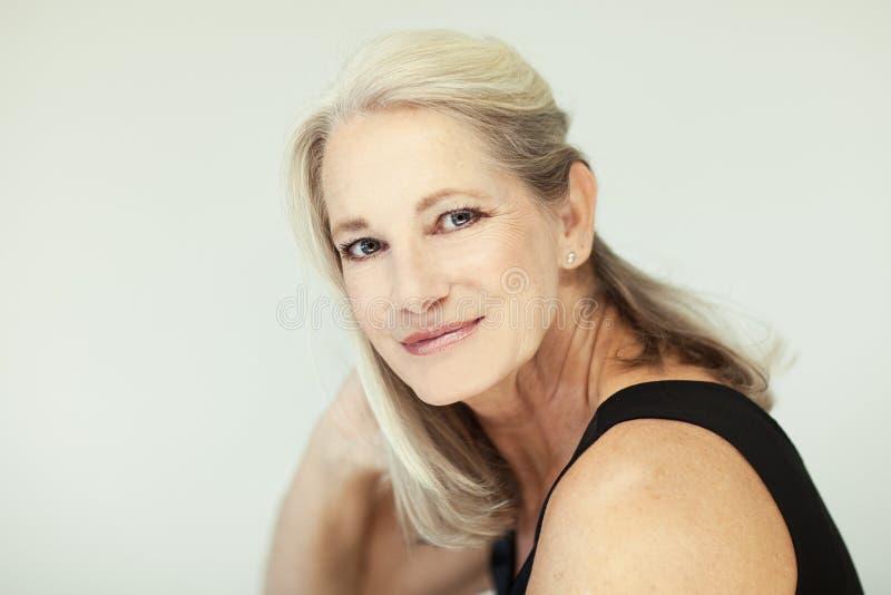 Het overweldigen van mooie en zelf zekere beste oude vrouw die met grijs haar in camera glimlachen stock afbeelding