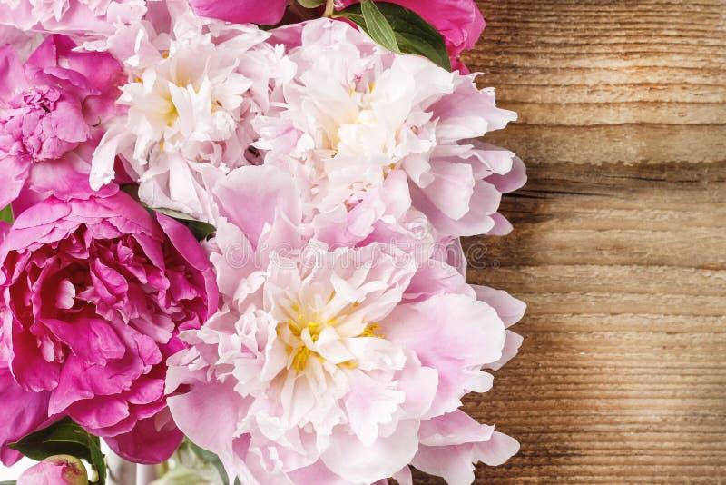 Het overweldigen van roze pioenen op rustiek hout stock foto