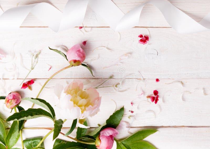 Het overweldigen van roze pioenen op witte rustieke houten achtergrond De ruimte van het exemplaar royalty-vrije stock afbeeldingen