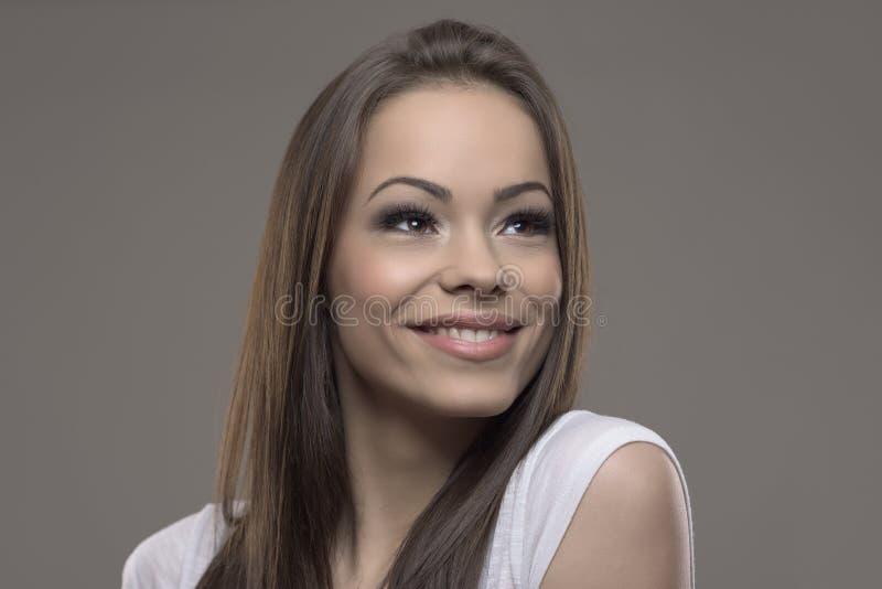 Het overweldigende donkerbruine schoonheids jonge vrouw zorgvuldig glimlachen en het kijken omhoog stock afbeeldingen
