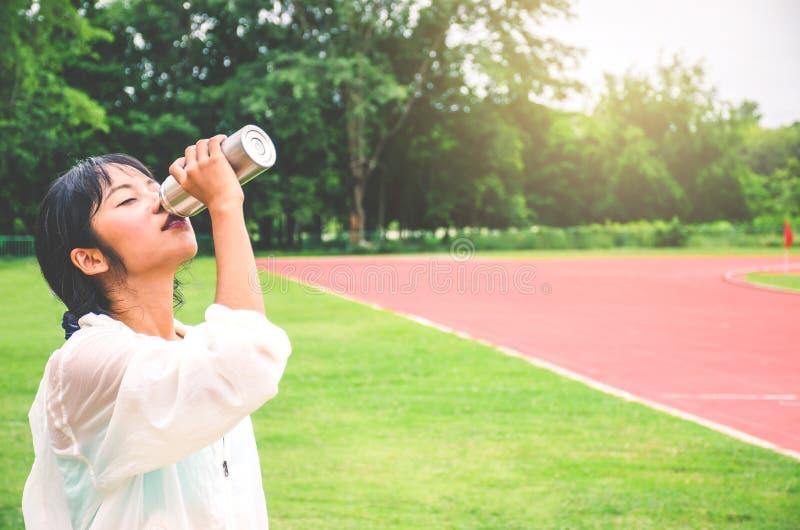 Het overweldigende drinkwater van de geschiktheidsvrouw van fles tijdens het lopen bij het stadion in zonnige ochtend Lege ruimte stock foto's