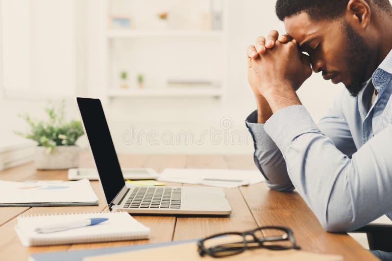 Het overwerken van Afrikaans-Amerikaanse werknemer zich op het werk stock foto