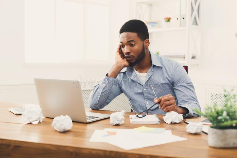 Het overwerken van Afrikaans-Amerikaanse werknemer zich op het werk stock afbeelding