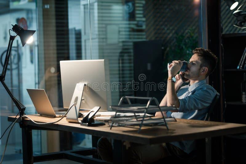 Het overwerken vanzich mens die met koffie op telefoon de spreken royalty-vrije stock afbeelding