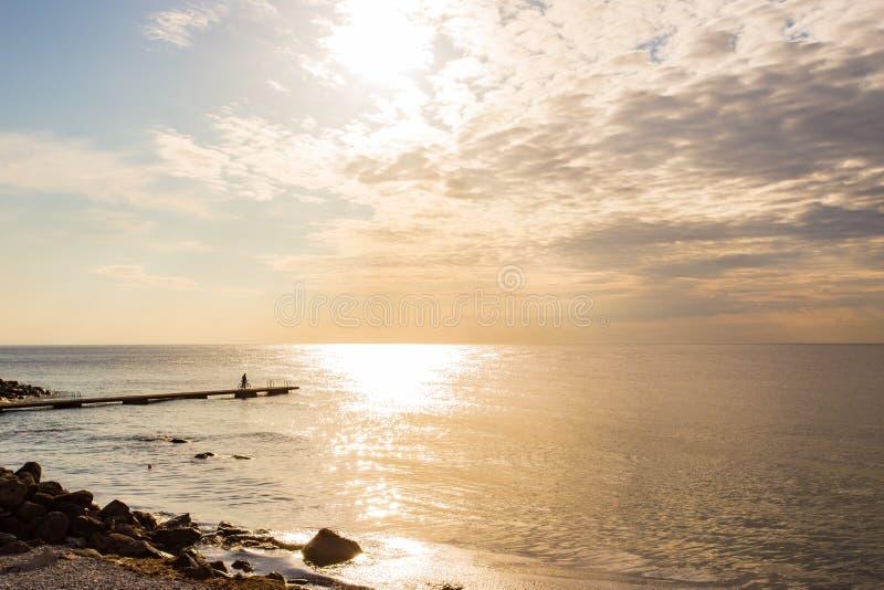 Het overzees, de fietser op de pijler, het silhouet Scandinavië, Zweden royalty-vrije stock fotografie