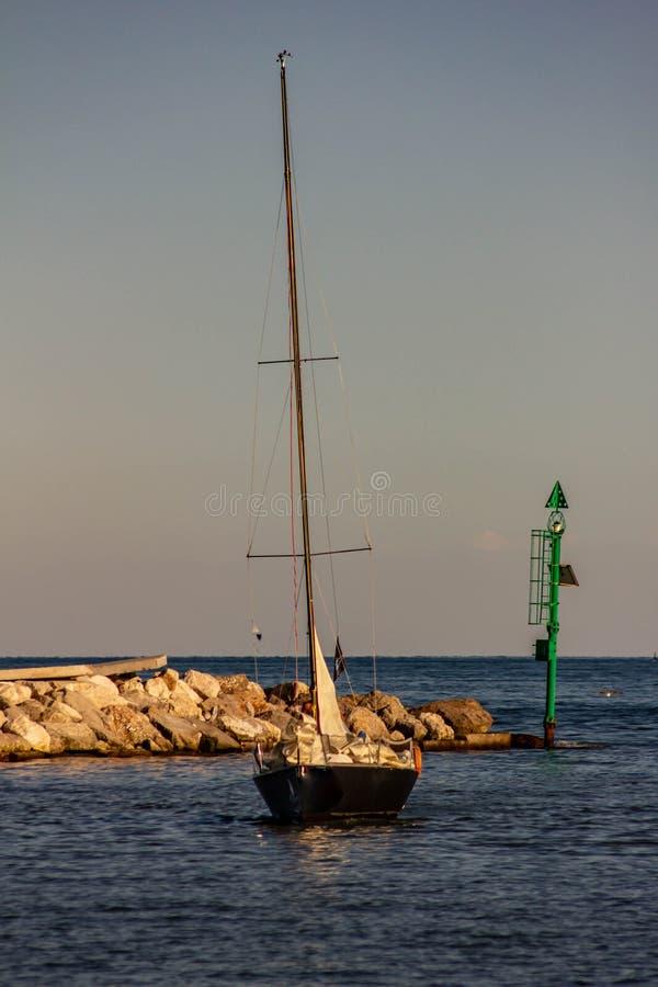 Het overzees, de zon is bijna bij zonsondergang, keert een zeilboot naar haven na een gang terug Mooie achtergrond royalty-vrije stock afbeeldingen
