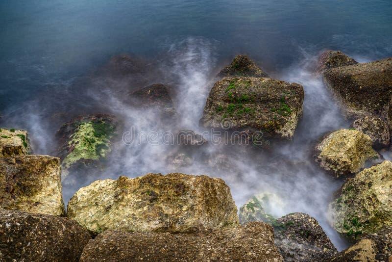 Het overzees die rotsen raken snakt blootstellingsschot royalty-vrije stock fotografie