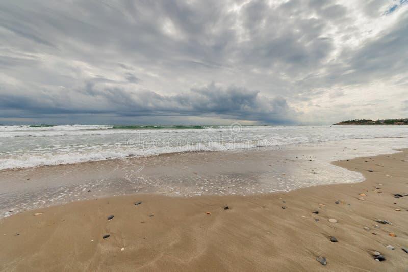 Het overzees van het strand onder een onweershemel stock afbeelding