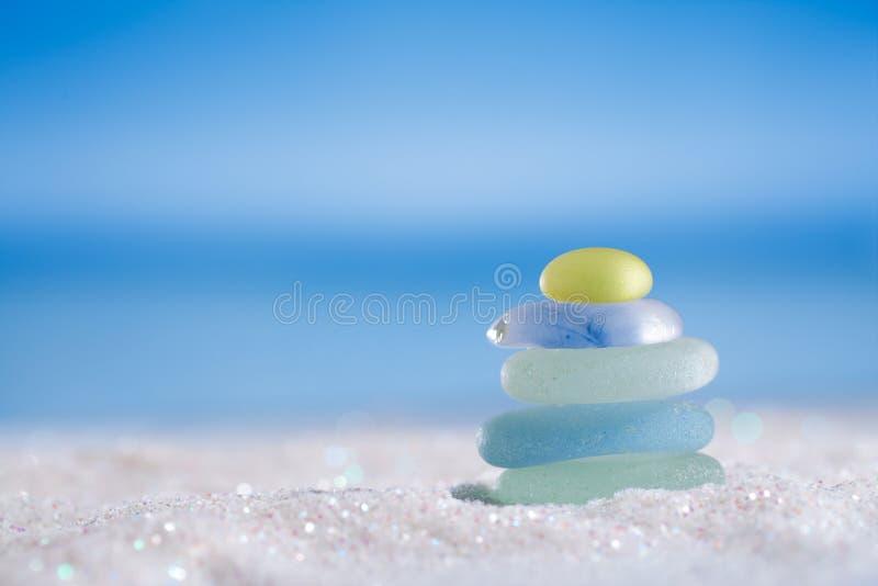 Het overzeese glas seaglass schittert zand met oceaan, strand en seasca stock afbeeldingen