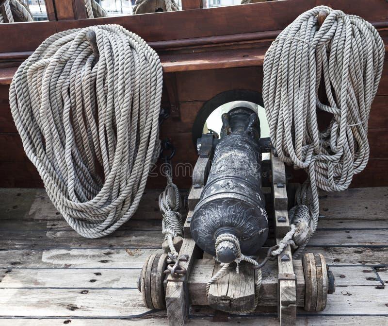 Het overzeese kanon Het oude schipkanon, de kabels aan de kant van het schip Een piraatschip stock afbeelding