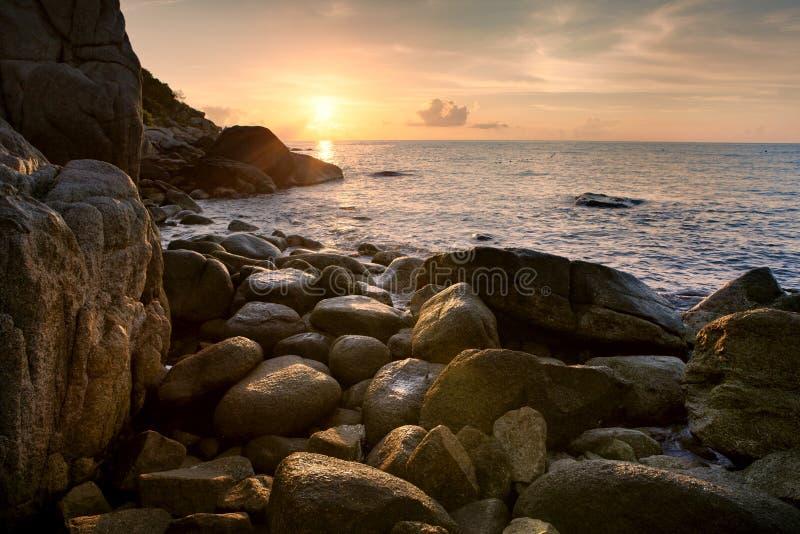 Het overzeese scape zon toenemen hemel op verlaten rotsstrand stock foto's