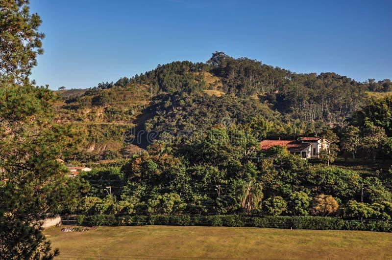 Het overzicht van heuvels met hout en huis in de zonsopgang, dichtbij Monte Alegre doet Sul royalty-vrije stock foto's