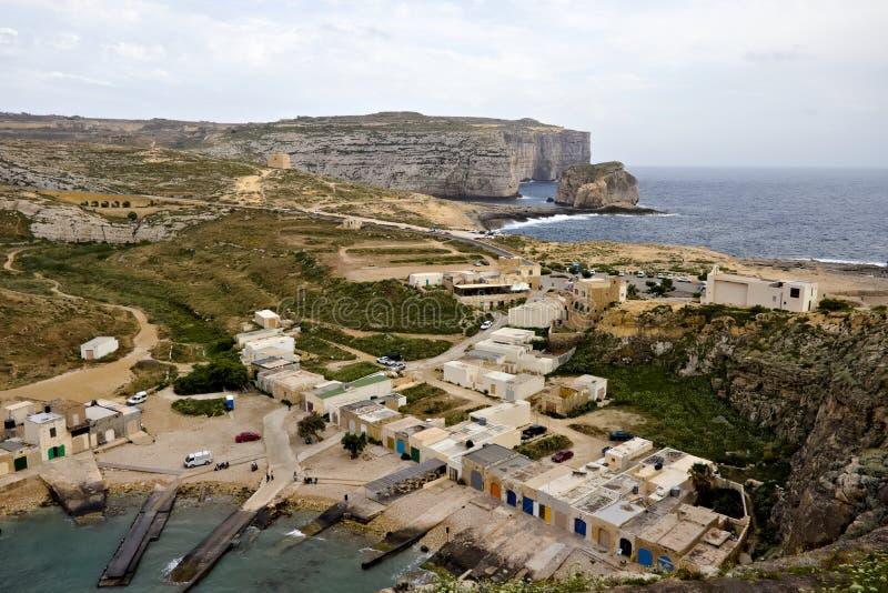 Het overzien van binnenlandse overzees met kleine huizen naast het en paddestoelrots op de achtergrond in gozo, Malta royalty-vrije stock foto