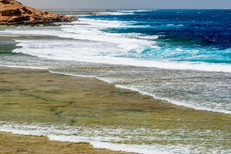 Het overzien van Brede Coral Reef met Grote Schuimgolven en Eenzame Pijlers in Calimera Habiba Beach Resort stock afbeelding