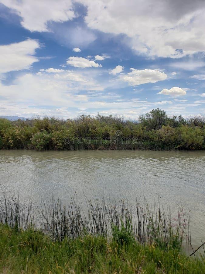 Het overzien van een modderig rivier en woestijnlandschap onder blauwe hemel en wolken stock fotografie