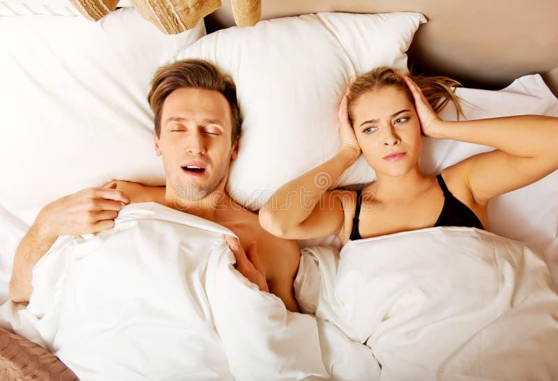 Het paar in bed, man het snurken vrouw kan niet slapen royalty-vrije stock afbeeldingen