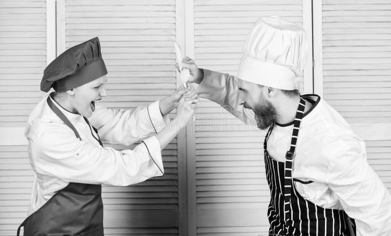 Het paar concurreert in culinaire arts. Keukenregels Who betere kok Culinair slagconcept Culinaire vrouw en gebaarde man stock foto