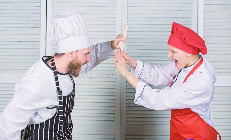 Het paar concurreert in culinaire arts. Keukenregels Who betere kok Culinair slagconcept Culinaire vrouw en gebaarde man royalty-vrije stock afbeelding