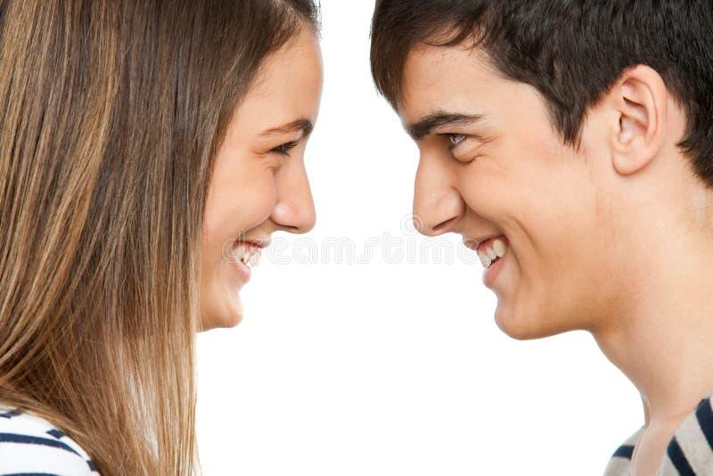 Het paar dat van de tiener elkaar onder ogen ziet het glimlachen. royalty-vrije stock afbeelding