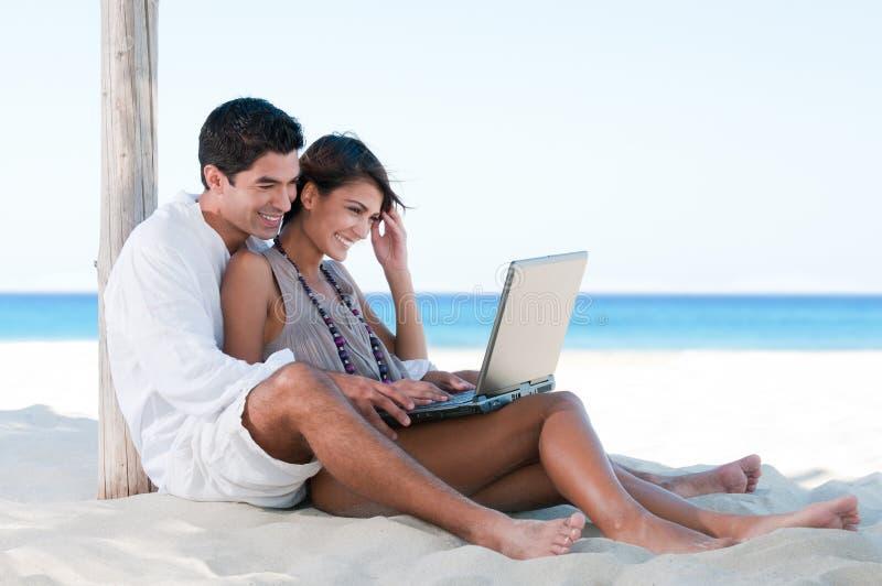 Het paar dat van de zomer laptop met behulp van royalty-vrije stock afbeeldingen