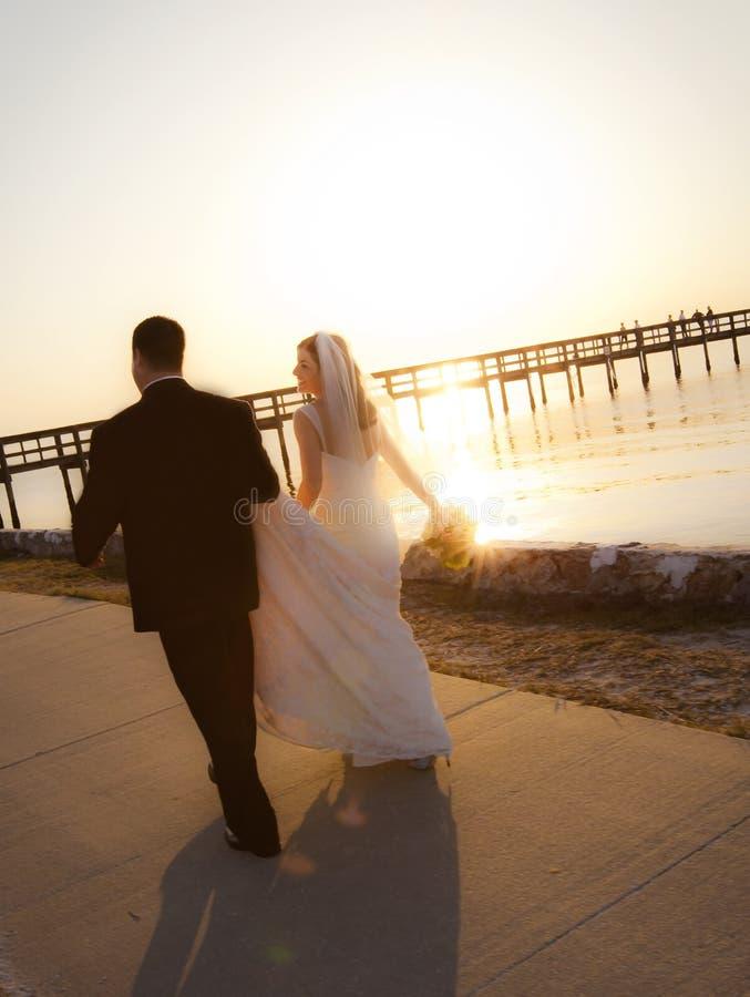 Het paar dat van het huwelijk in zonsondergang loopt royalty-vrije stock foto's