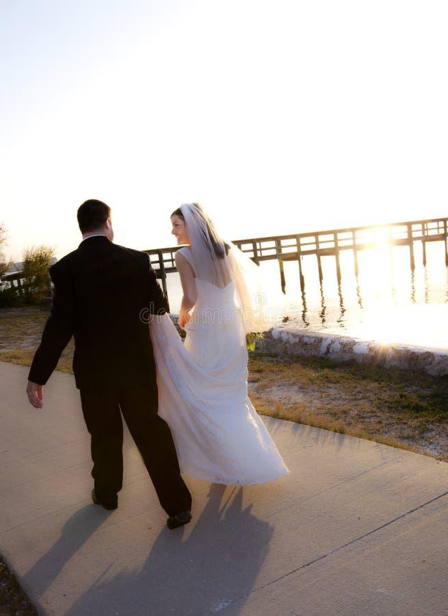 Het paar dat van het huwelijk in zonsondergang loopt stock fotografie