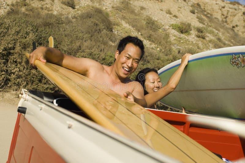 Het paar dat van Surfer surfplanken van rug van vrachtwagen neemt stock afbeelding