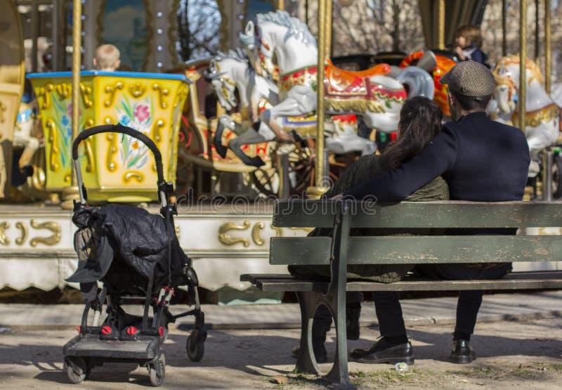 Het paar dichtbij de carrouselzitting op de bank die op een kind wachten berijdt carrousel stock afbeeldingen