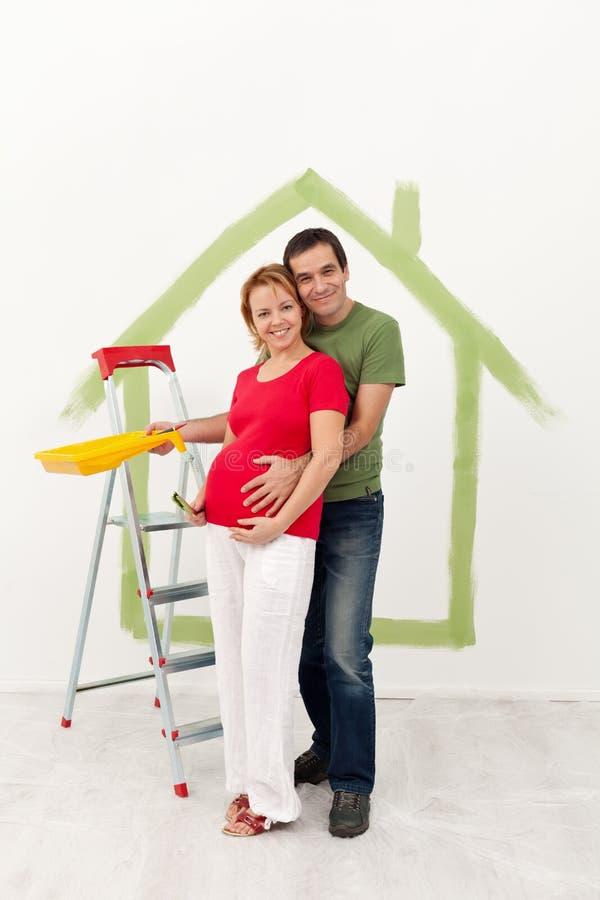 Het paar die een baby verwachten knapt hun nieuw huis op stock afbeelding