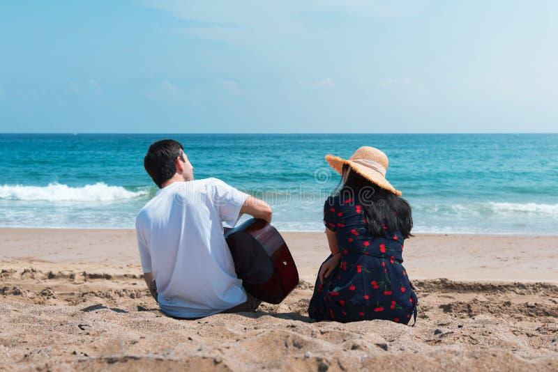 Het paar die en het spelen gitaar koopt het strand zingen stock foto's