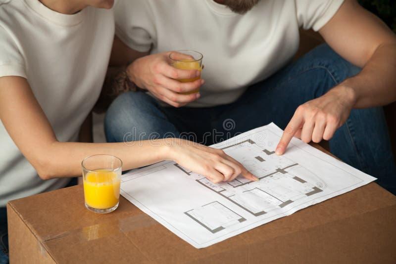 Het paar die over binnenlands ontwerp met huisplan spreken, close-up wedijvert royalty-vrije stock afbeelding