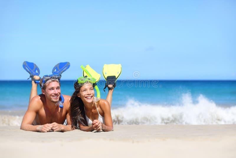 Het paar die van de strandreis pret het snorkelen het kijken hebben stock afbeelding