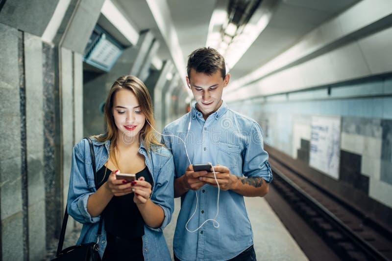 Het paar die van de telefoonverslaafde gadget in metro gebruiken stock fotografie