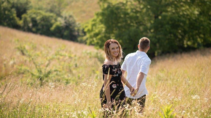 Het paar die van de de zomerliefde op grasrijk gebied lopen royalty-vrije stock fotografie