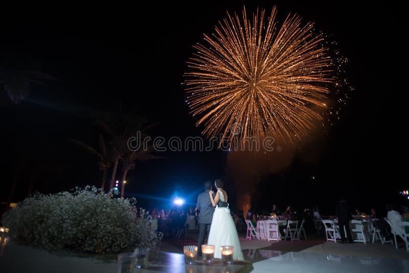 Het paar die van het het huwelijksvuurwerk van het bestemmingsstrand bekijken royalty-vrije stock foto