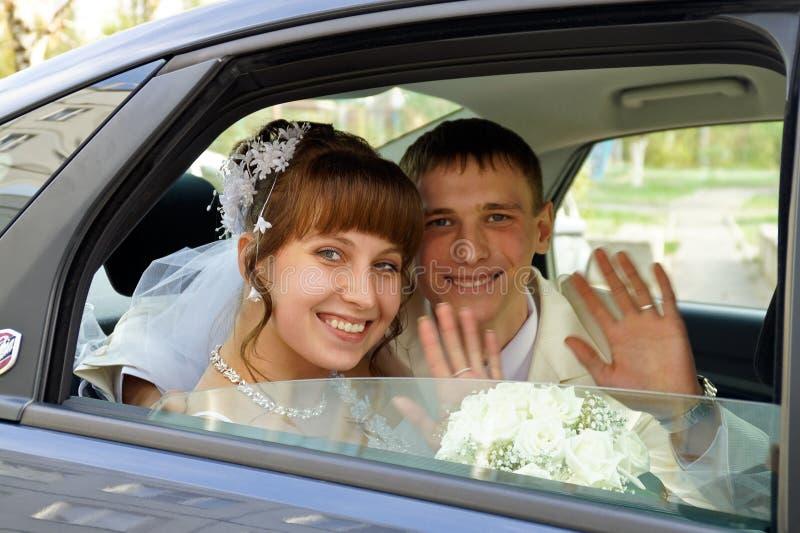 Het paar in een huwelijksauto stock afbeeldingen
