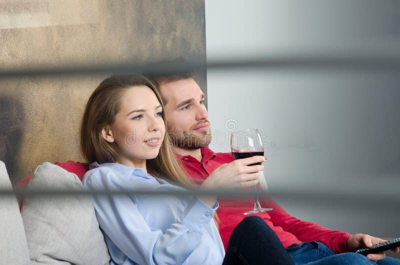 Het paar geniet vrije tijd en het letten op van TV stock afbeeldingen