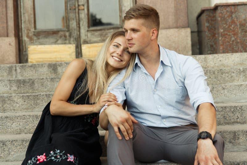 Het paar glimlacht en zit op de stappen, het koesteren, het dateren Liefde royalty-vrije stock foto's
