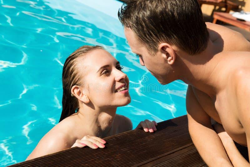 Het paar heeft een rust in de pool met champagne zij glimlachen, koesteren en kussen stock afbeeldingen