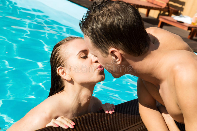 Het paar heeft een rust in de pool met champagne zij glimlachen, koesteren en kussen royalty-vrije stock foto
