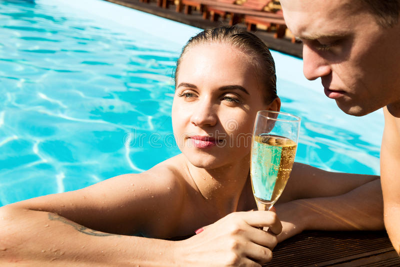 Het paar heeft een rust in de pool met champagne zij glimlachen, koesteren en kussen stock foto's