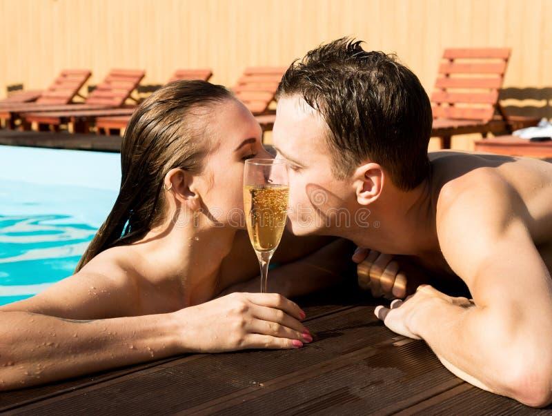 Het paar heeft een rust in de pool met champagne zij glimlachen, koesteren en kussen royalty-vrije stock foto's
