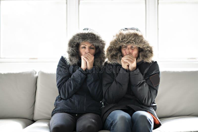 Het paar heeft koude thuis op de bank met de winterlaag stock afbeeldingen