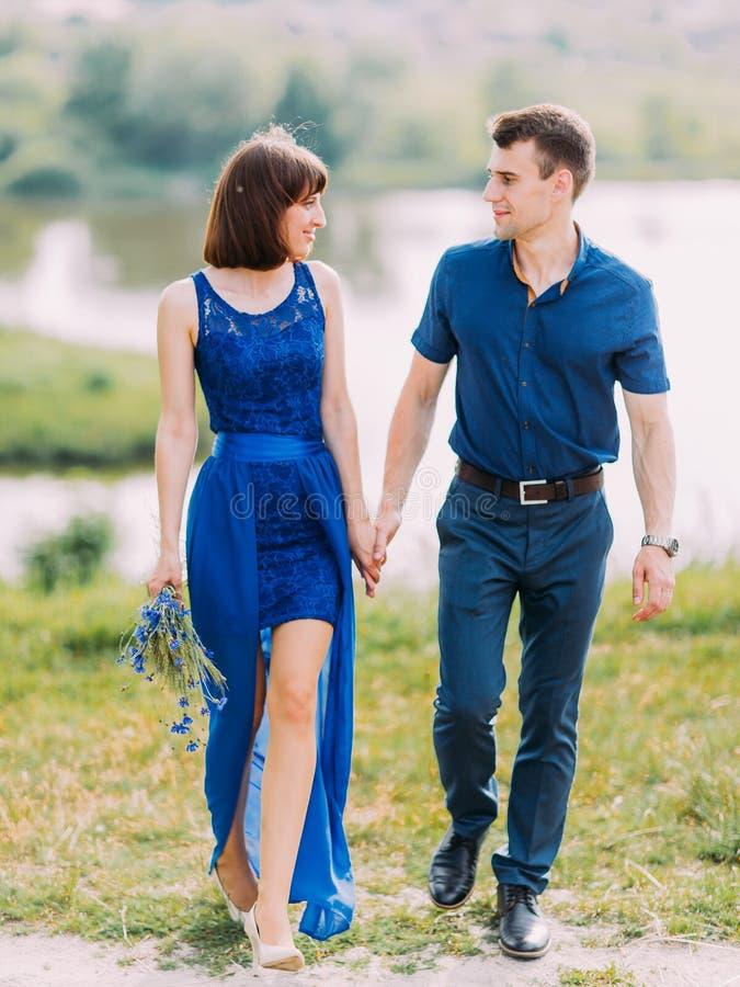 Het paar houdt handen en bekijkt elkaar terwijl het lopen in de weide De mening van gemiddelde lengte royalty-vrije stock fotografie