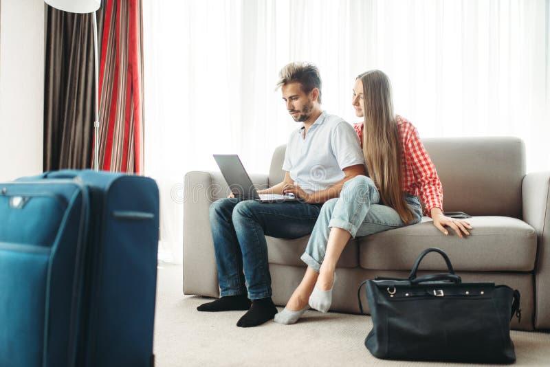 Het paar kijkt op laptop het scherm, prijzen op reis stock foto