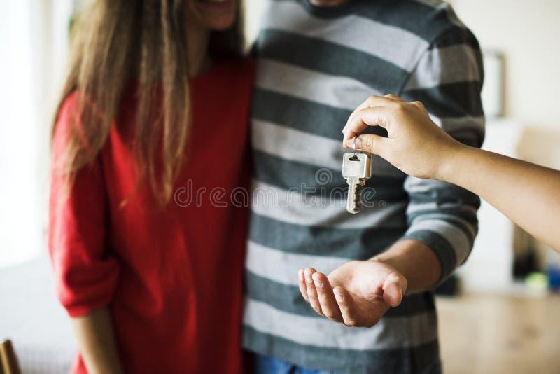 Het paar kocht nieuw huissleutels die worden overhandigd stock foto