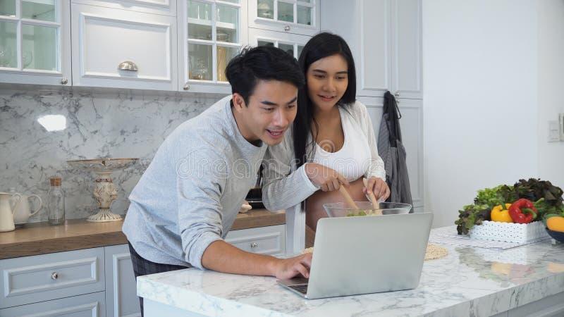 Het paar kookt samen gelukkig met laptop computer royalty-vrije stock fotografie