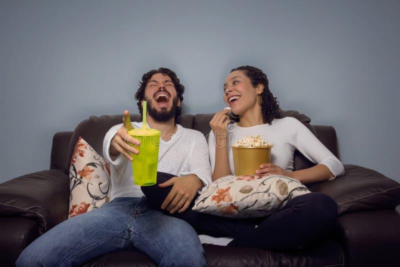 Het paar lacht en let op film Pret thuis, vrije tijd stock afbeeldingen