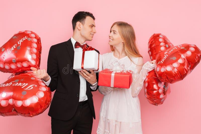 Het paar in liefde, een man en een vrouw geven elkaar giften, de dozen van de greepgift en ballons, in de studio op een roze acht royalty-vrije stock afbeeldingen