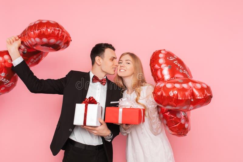 Het paar in liefde, een man en een vrouw geven elkaar giften, de dozen van de greepgift en ballons, in de studio op een roze acht stock afbeelding